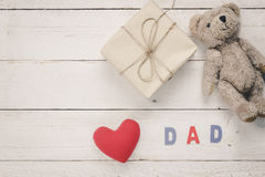 Top view Happy Father day.Red heart with word. `DAD` on wooden background.Present and Bear doll for gifts Stock Images
