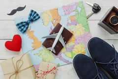 Top view Happy Father day with travel concept. Airplane and passport on map and rustic wooden background. accessories with red heart,mustache,vintage bow tie Royalty Free Stock Images