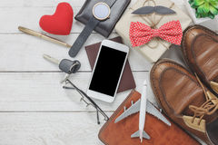 Top view Happy Father day with travel concept. Mobile phone and passport on rustic wooden background. accessories with airplane,mustache,vintage bow tie,pen Royalty Free Stock Photo