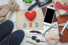 Top view Happy Father day with travel concept. Red heart and word `DAD with paper on rustic wooden background. accessories with ,passport,airplane,mustache Stock Photos