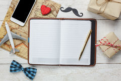 Top view Happy Father day with travel. White mobile phone and notebook on rustic wooden background.accessories with ,map,airplane,mustache,vintage bow tie,pen Stock Photo