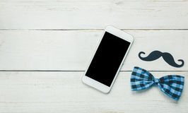 Top view Happy Father day.White mobile phone on rustic wooden. Top view Happy Father day.White mobile phone on rustic wooden background.Sign father is mustache Stock Image