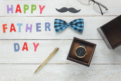 Top view Happy Father`s day concept. Pen with word `HAPPY FATHER DAY` on wooden background.accessories with mustache,vintage bow tie,eyeglasses and present `s Royalty Free Stock Image