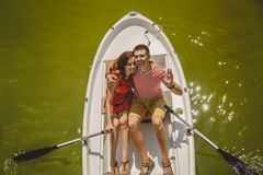 Top view of happy loving couple rowing a small boat on a lake. A fun date in nature. Couple hugging in a boat. Stock Photo