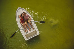 Top view of happy loving couple rowing a small boat on a lake. A fun date in nature. Couple hugging in a boat. Stock Images