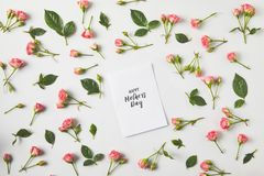 Top view of happy mothers day greeting card and beautiful pink roses and green leaves on grey royalty free stock image