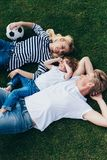 Top view of happy parents with cute little son holding soccer ball while lying. On green grass royalty free stock photo
