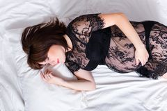 Happy pregnant woman sleeping in bed Stock Photography