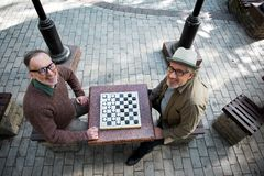 Joyful mature male pensioners entertaining with draughts Royalty Free Stock Image