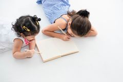 Top view of happy two sister drawing in sketch book together at home or nursery. People lifestyle and kids play. Education and. Children concept. Diverse royalty free stock images