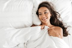 Top view of a happy young asian woman lying in bed. And holding a blanket Stock Image