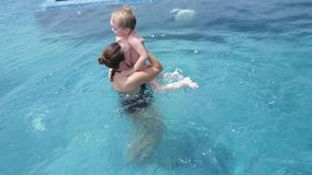 Top of view of happy young mother and her little son, adorable laughing boy having fun together in an outdoor swimming stock video