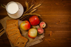 Top view, harvest on a wooden table: apples, peaches, rye bread, a jug of milk, ears on sackcloth Royalty Free Stock Photos