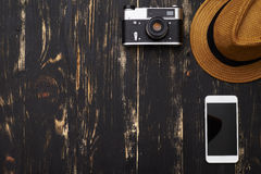 Top view of hat, old-fashioned camera and smartphone on wooden t Stock Photography