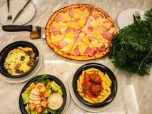 Top view Hawaiian pan pizza, meatball penne and caesar salad in restaurant. Top view of Hawaiian pan pizza, meatball penne and caesar salad in restaurant royalty free stock photo