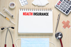 Top view of Health Insurance with notebook, stethoscope, hypodermic syringe, plaster, gauze, medicine, tape and calculator.  royalty free stock images