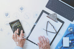 top view of Healthcare costs and fees concept.Hand of smart doctor used a calculator for medical costs in modern hospital with royalty free stock image