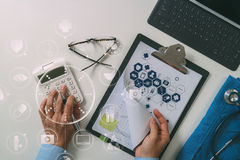 Top view of Healthcare costs and fees concept.Hand of smart doct. Or used a calculator for medical costs in modern hospital with VR icon diagram Royalty Free Stock Photo
