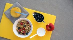 Healthy breakfast with granola, greek yogurt, apple, berries and fresh orange juice on yellow cutting board on gray tablecloth stock image