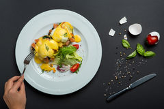Top view of healthy breakfast with poached eggs royale, benedict with salmon and green salad on black royalty free stock images