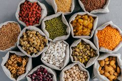 Top view of healthy dry ingredients in burlap bags. Nutritious cereals and dried fruit: almond, garbanzo, pistache, goji,. Buckwheat, mulberry, legume in cloth royalty free stock images