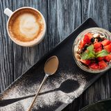 Top view of healthy fruity dessert, spoon and cup of coffee. On wooden table Royalty Free Stock Photography