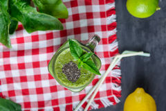 Top view Healthy green spinach smoothie in a jar mug decorated with mint and chia seeds with ingredients on the checkered red napk. In on the black wooden table Stock Photos