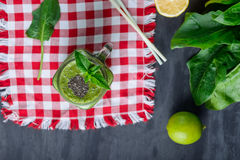 Top view Healthy green spinach smoothie in a jar mug decorated with mint and chia seeds with ingredients on the checkered red napk. In on the black wooden table Royalty Free Stock Photos