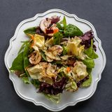 Top view of healthy organic salad on white plate on dark backgro Stock Images