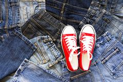 Top view Heap of blue jeans and red sneakers, Jeans background. Top view of Red Sneakers on Heap of blue jeans, Jeans background royalty free stock photography