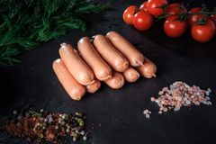 Top view on heap of long sausages with rucola and tomatoes. Top view on heap of raw long thick sausages with pink salt, spices, rucola and tomatoes cherry on royalty free stock image