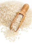 Top view of heap parboiled rice and wooden scoop on white background. stock photo
