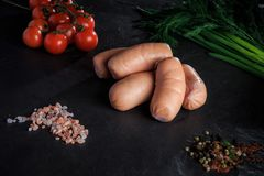 Top view on heap of short sausages with dill and tomatoes. Top view on heap of raw thick short sausages with pink salt, spices, green dill and tomatoes cherry on royalty free stock photos