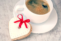 Top view of a heart shaped cookie with icing and red ribbon and a cup of coffee over a white wood rustic background. Love concept. Royalty Free Stock Photography