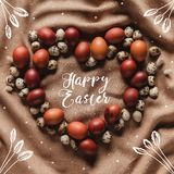 Top view of heart shaped frame made of chicken and quail eggs with Happy Easter lettering, stars. And floral illustration royalty free stock photo