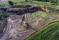 Top view heavy machine excavator bagger working in mud on construction site with green landscape surrounding Royalty Free Stock Images