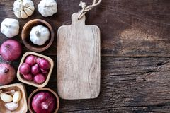 Top view of herbal vegetable ingredients, garlic, red onion, and empty chopping board on old wooden table, cooking preparation. Top view of herbal vegetable royalty free stock image