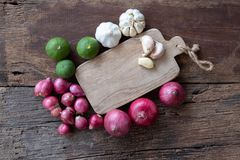 Top view of herbal vegetable ingredients, garlic, red onion, lime, lime leaf and chopping board on old wooden table, cooking. Preparation concept, copy space stock photos