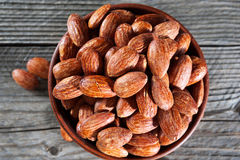 Top view of hickory smoked almonds in a small bowl on a wood table. Royalty Free Stock Image