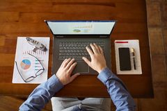 Top view of hipster vintage wooden desktop workplace. Male hands typing on a laptop. Businessman working on computer at. Office desk with paperwork, notebook Royalty Free Stock Photography