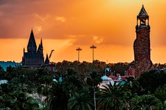Top view of Hogwarts Castle and Island of Adventure lighthouse on colorful sunset sky background at Universal Studios area 1 stock image