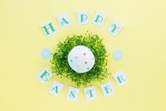 Top view holiday composition with green sprouts pillow and decorated easter cupcake on it, Happy Easter calligraphy lettering on b. Right yellow background. Art Royalty Free Stock Photo