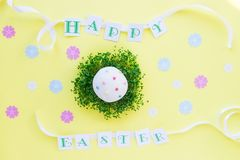 Top view holiday composition with green sprouts pillow and decorated easter cupcake, Happy Easter lettering with white ribbon on b. Right yellow background. Art Royalty Free Stock Photos
