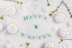 Top view holiday composition of Happy Easter lettering, branches with young shoots of greenery, decorated cupcakes, merengue sweet. S, bird figure on wooden Stock Images