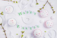 Top view holiday composition of Happy Easter lettering, branches with young shoots of greenery, decorated cupcakes, merengue sweet. S, bird figure on wooden Stock Photography