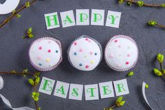 Top view holiday composition of Happy Easter lettering, branches with young shoots of greenery and three decorated cupcakes on dar. K stone background. Art Royalty Free Stock Images
