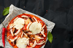 Top view of home made thin fresh italian pizza. Top view of homemade thin fresh italian pizza served on paper and black background Royalty Free Stock Photo