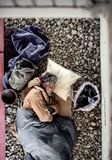 A top view of homeless beggar man lying on the ground outdoors in city, sleeping. royalty free stock image