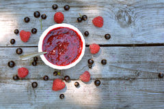 Top view of homemade, blended raspberry and blackcurrant jam and scattered berries. On grey, wooden table Stock Images