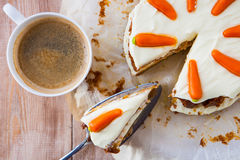 Top view of a homemade carrot cake with mascarpone cream cheese. Icing and handmade mini marzipan carrot decorations with a cup of hot black coffee royalty free stock photography